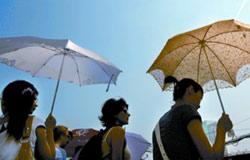 行人纷纷撑起遮阳伞